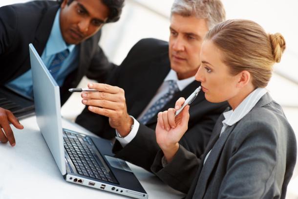 Business people around laptop