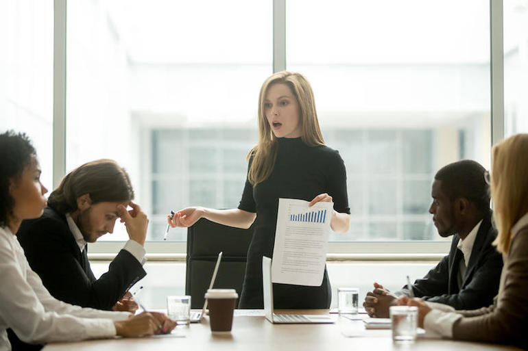 Dissatisfied female executive scolding employees for bad work at meeting