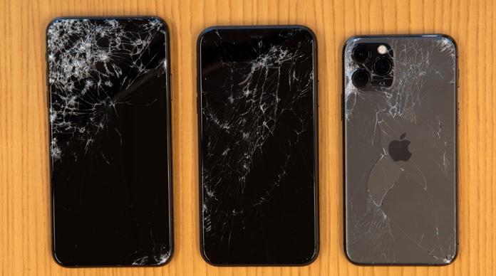 A lineup of broken iPhone 11 handsets