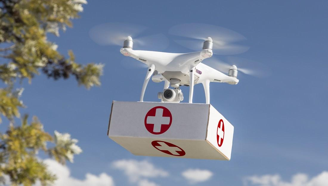 Unmanned Aircraft System (UAS) Quadcopter Drone Carrying First Aid Package In The Air.