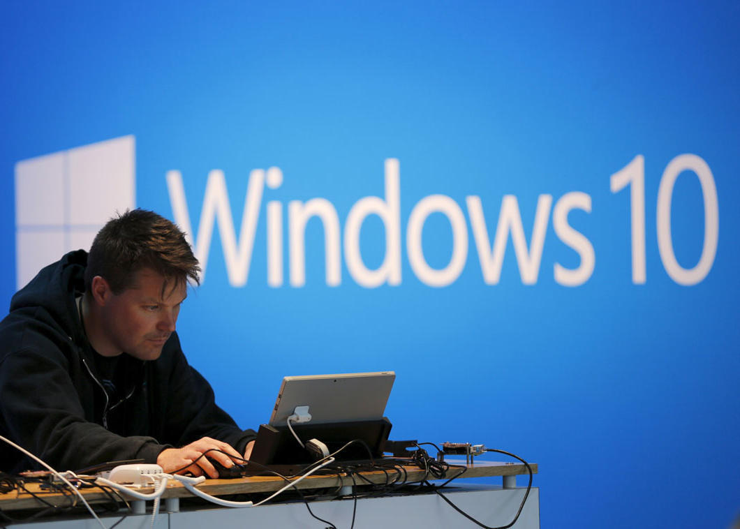 A man works on a laptop computer near a Windows 10 display at Microsoft Build in San Francisco