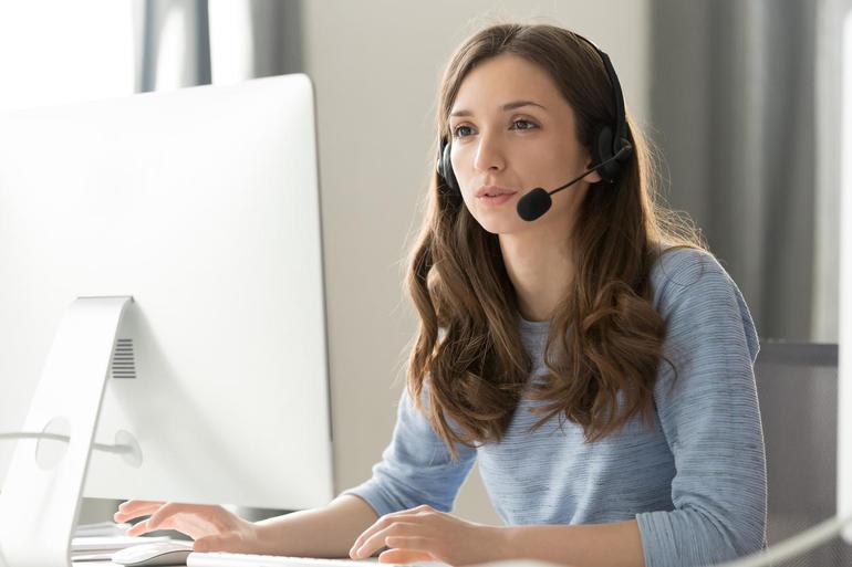 زن بازرگان در نمایندگی مرکز تماس هدست که از کنفرانس ویدئویی شرکت می کند