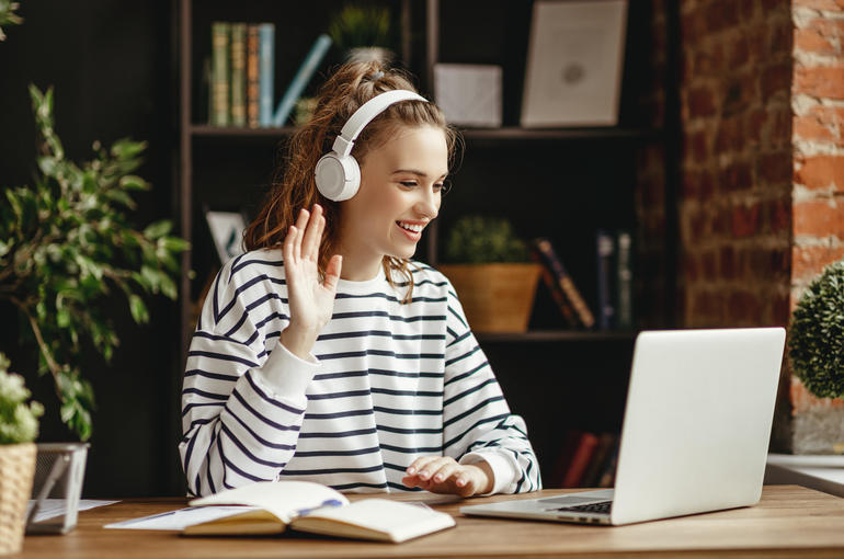 Cheerful woman in headphones greeting friend while talking on laptop at home