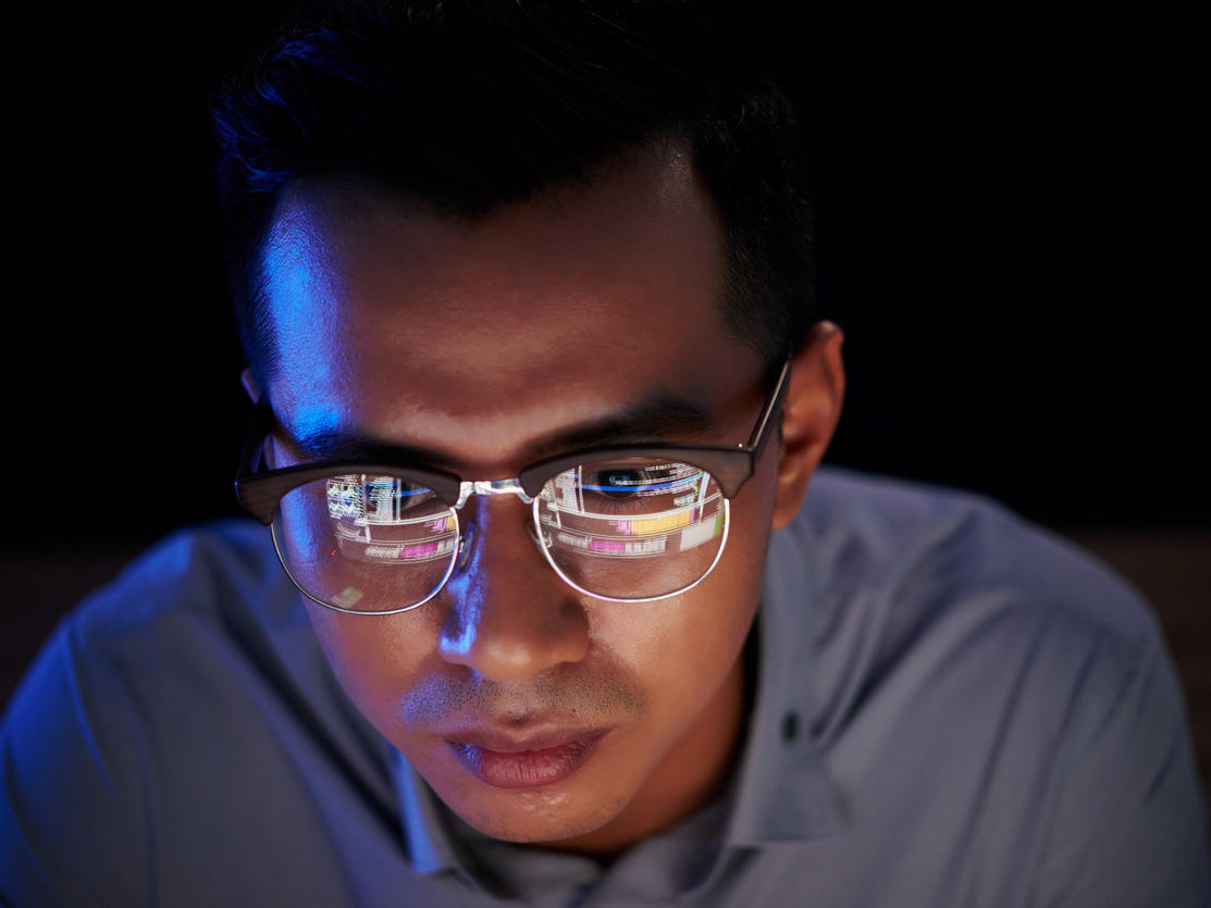 Software developer with programming code reflecting in his glasses