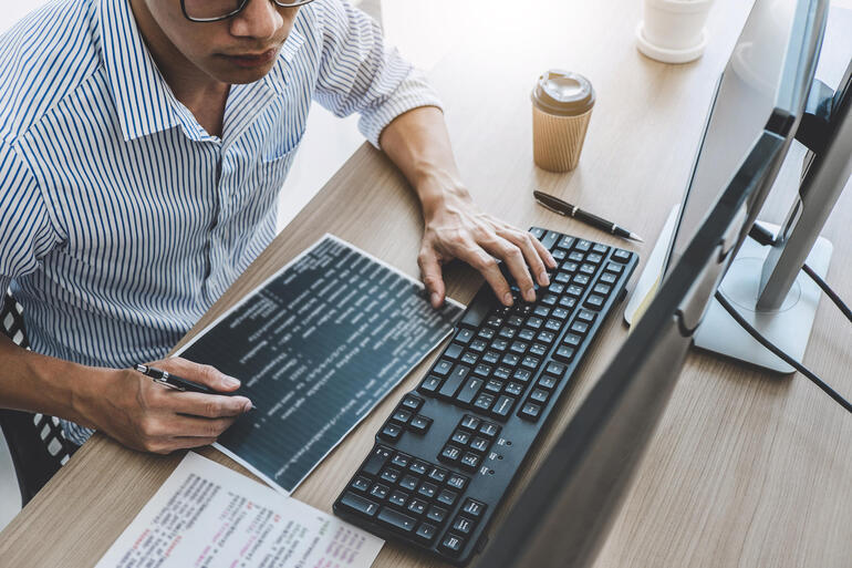 Professional programmer working at developing programming and website working in a software develop company office, writing codes and typing data code