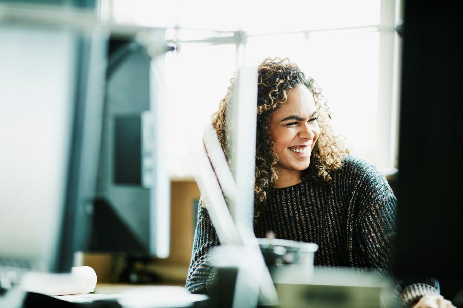 young-woman-employee-working-desk-office-laughing.jpg