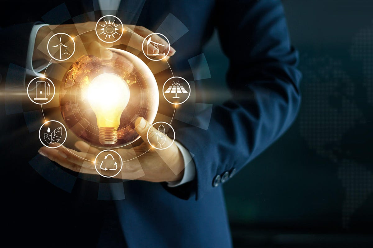 Businessman' s hand holding glowing light bulb with energy sources icon. Campaigning for ecological friendly and sustainable environment. Earth day. Energy saving concept, Elements of this image furnished by NASA