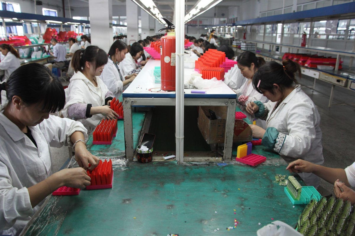 Chinese workers assembling lighters in factory.