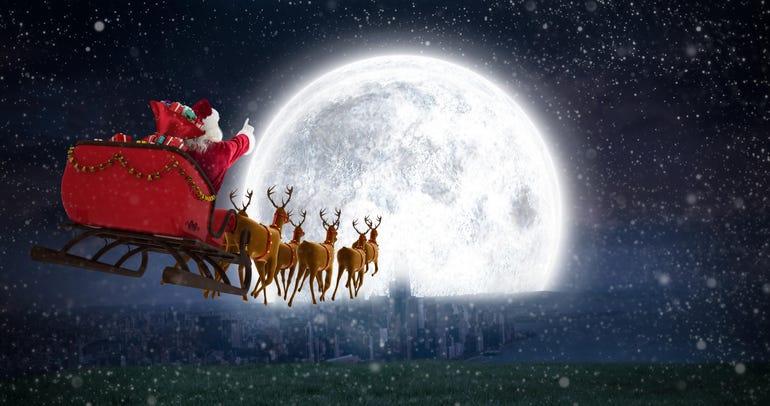Santa Claus riding on sleigh against bright moon