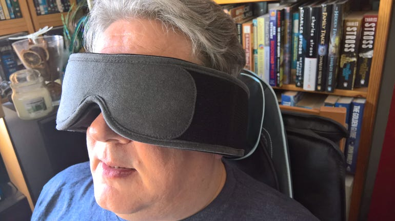 man in Silentmode sleep mask sitting in a chair