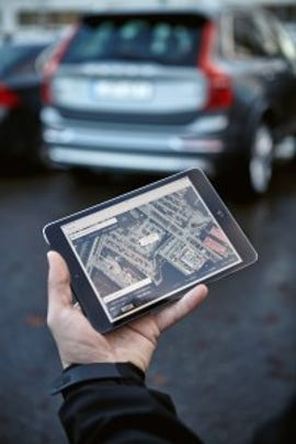 The deliveryman uses a map on a tablet to find your car