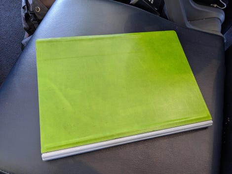 A green leather skin on the bottom of a Surface Book laptop