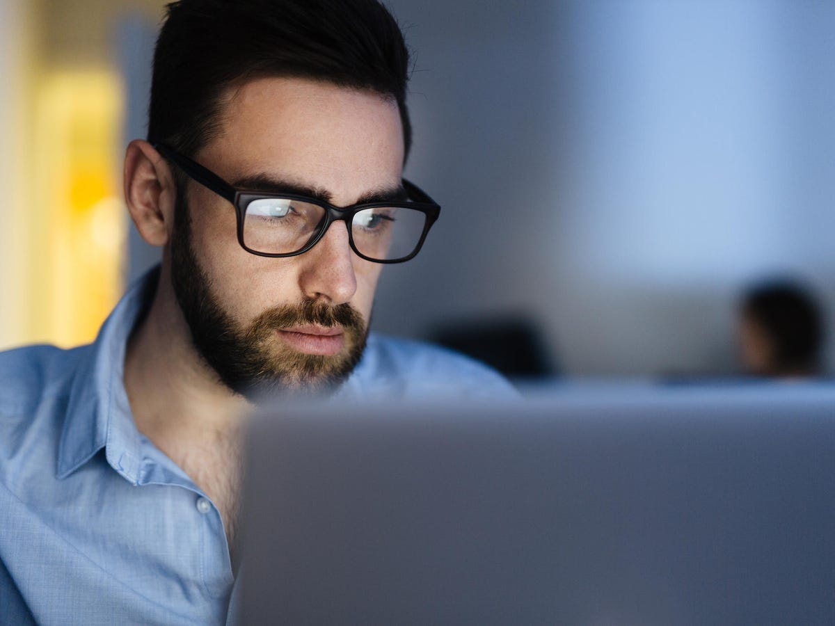 Computer user wearing glasses working with laptop