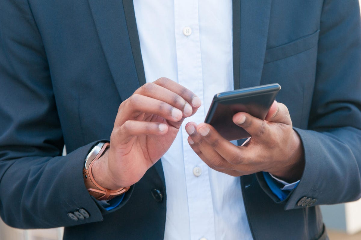 Closeup of mobile phone in business man hands
