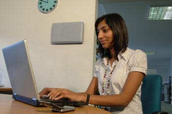 A woman sat at a laptop, with a Motorola 3G signal amplifier behind her