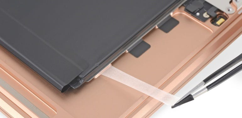 Stretch-release adhesive securing the battery in place