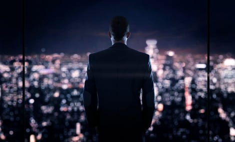 Businessman looking at the the city at night