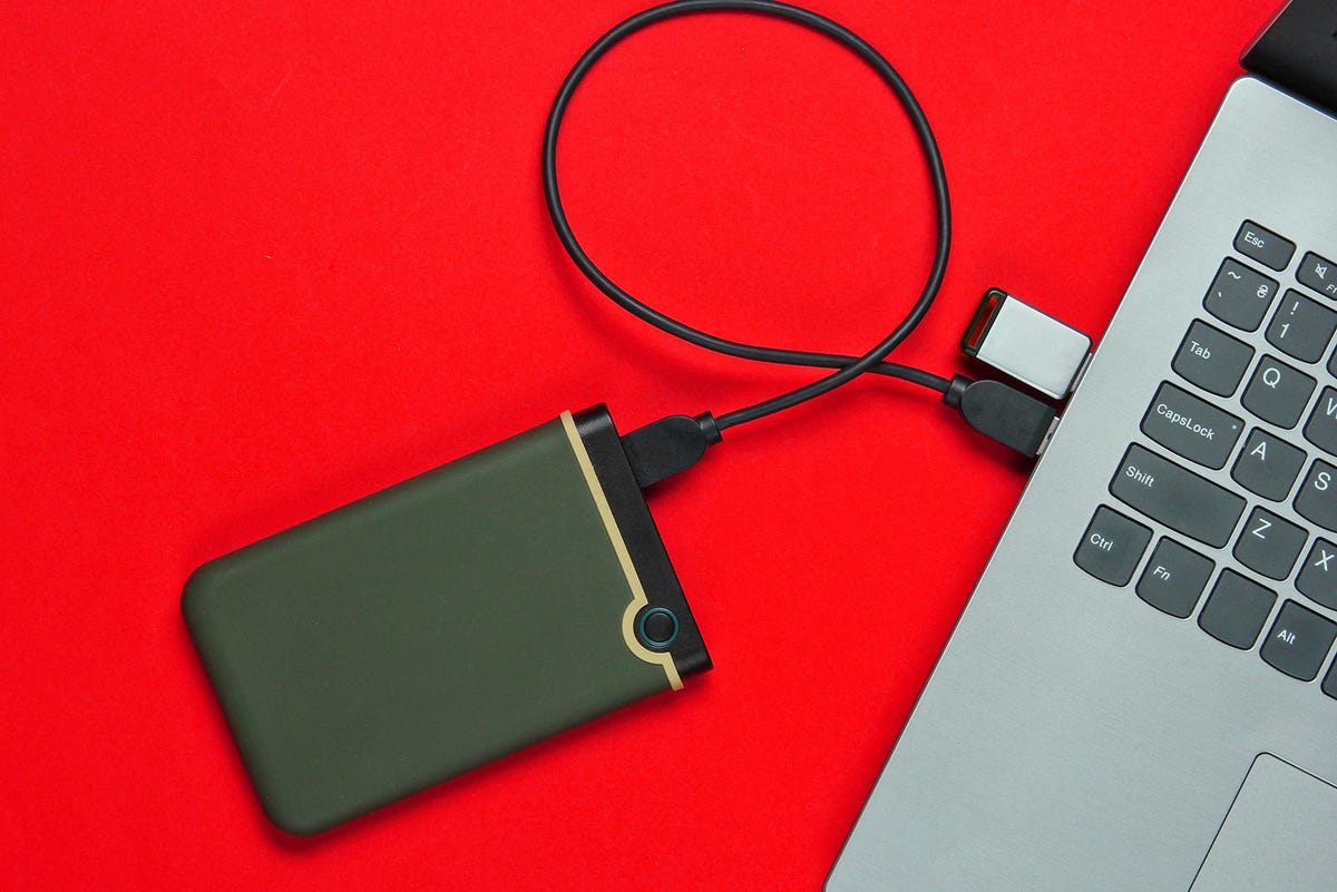 """Laptop with flash drive, external hard drive""""n on brown paper background. Studio shot, top view."""