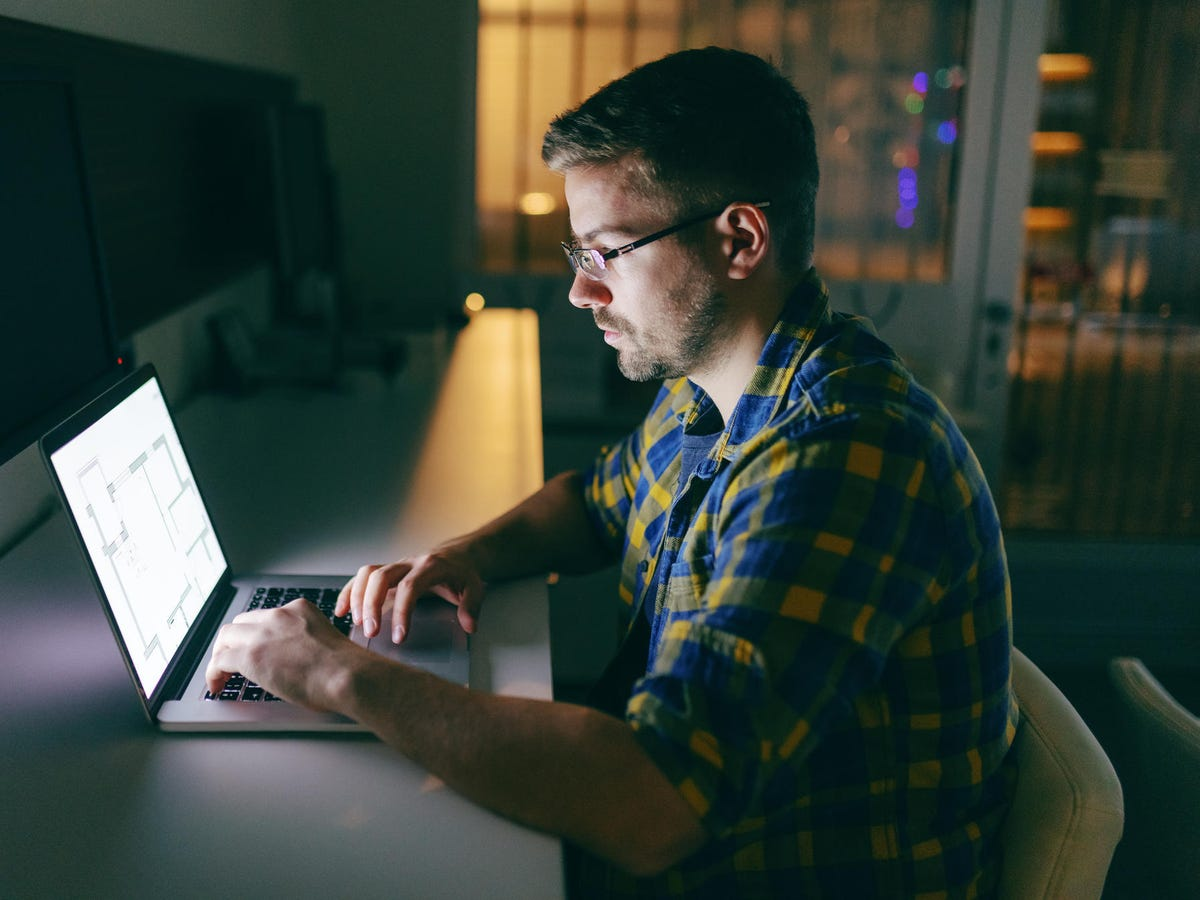 Developer using laptop in the office late at night.