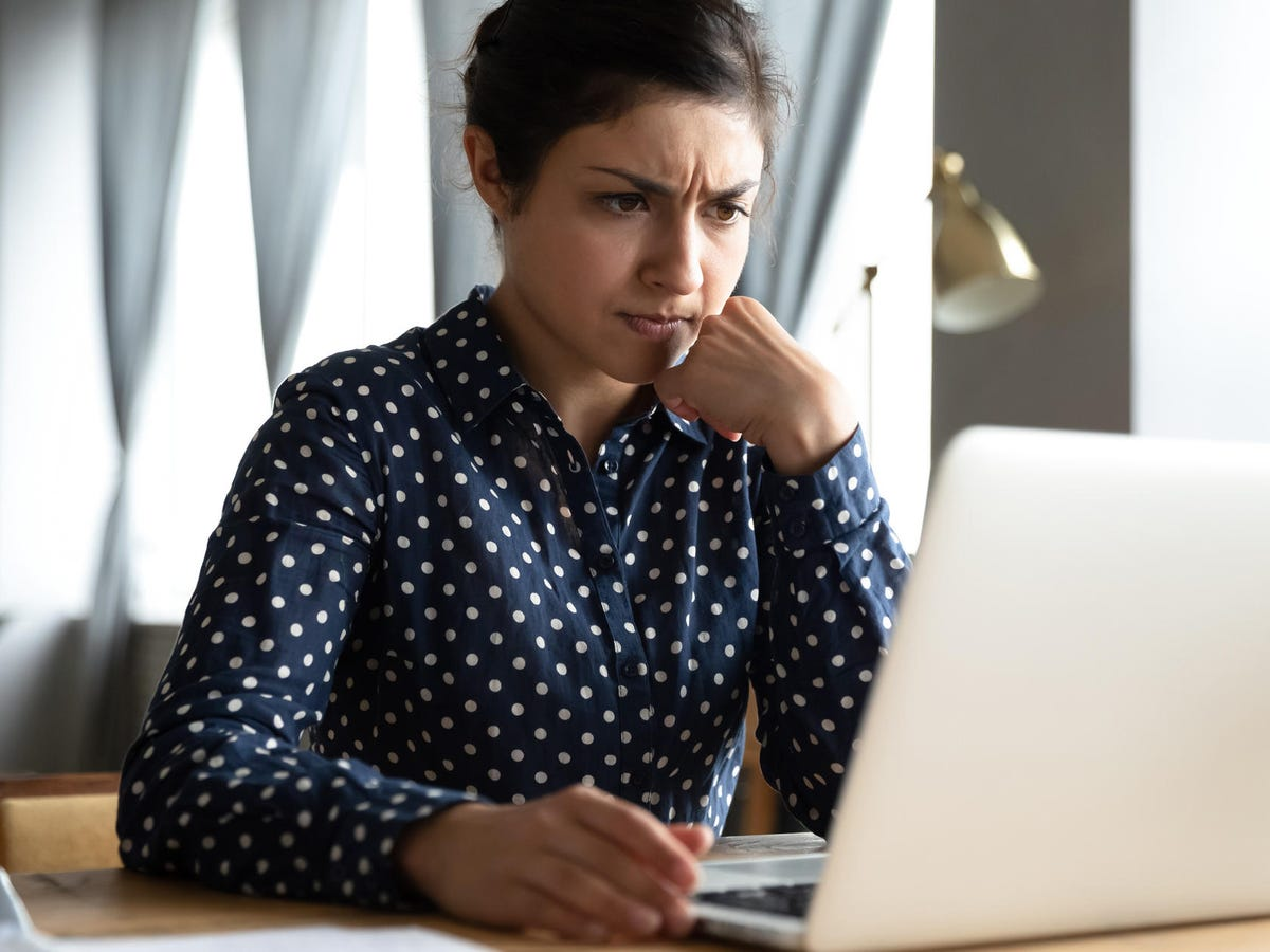 Computer user looking at laptop with concerned expression