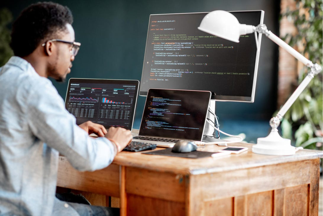 A Black person works at a desk with multiple computer monitors.