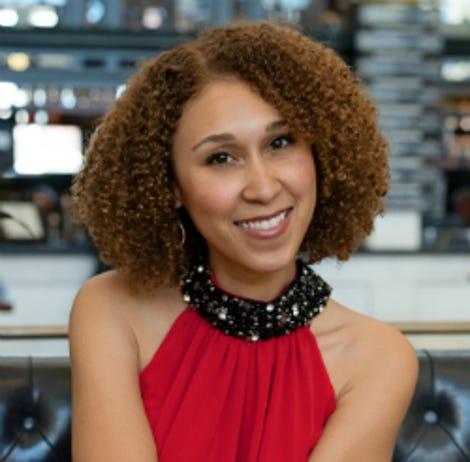 Krystal Covington, a woman with medium-length, curly hair, smiles at the camera.