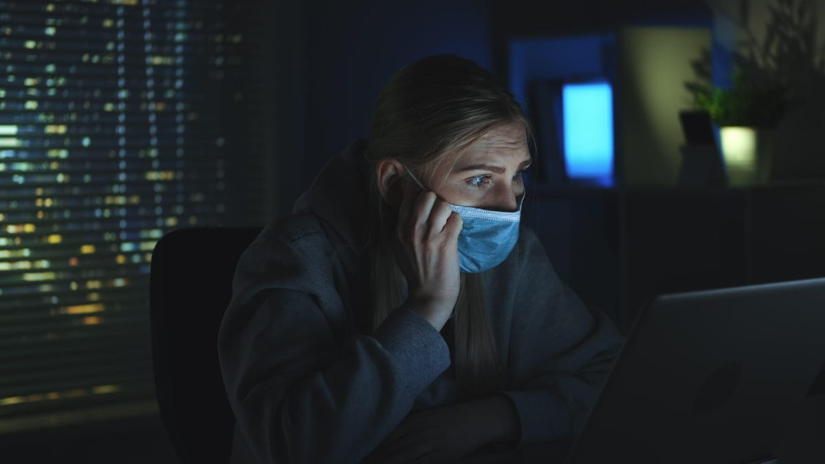 Close-up shot of Scared woman in medical mask reading news about coronavirus on laptop in darkness