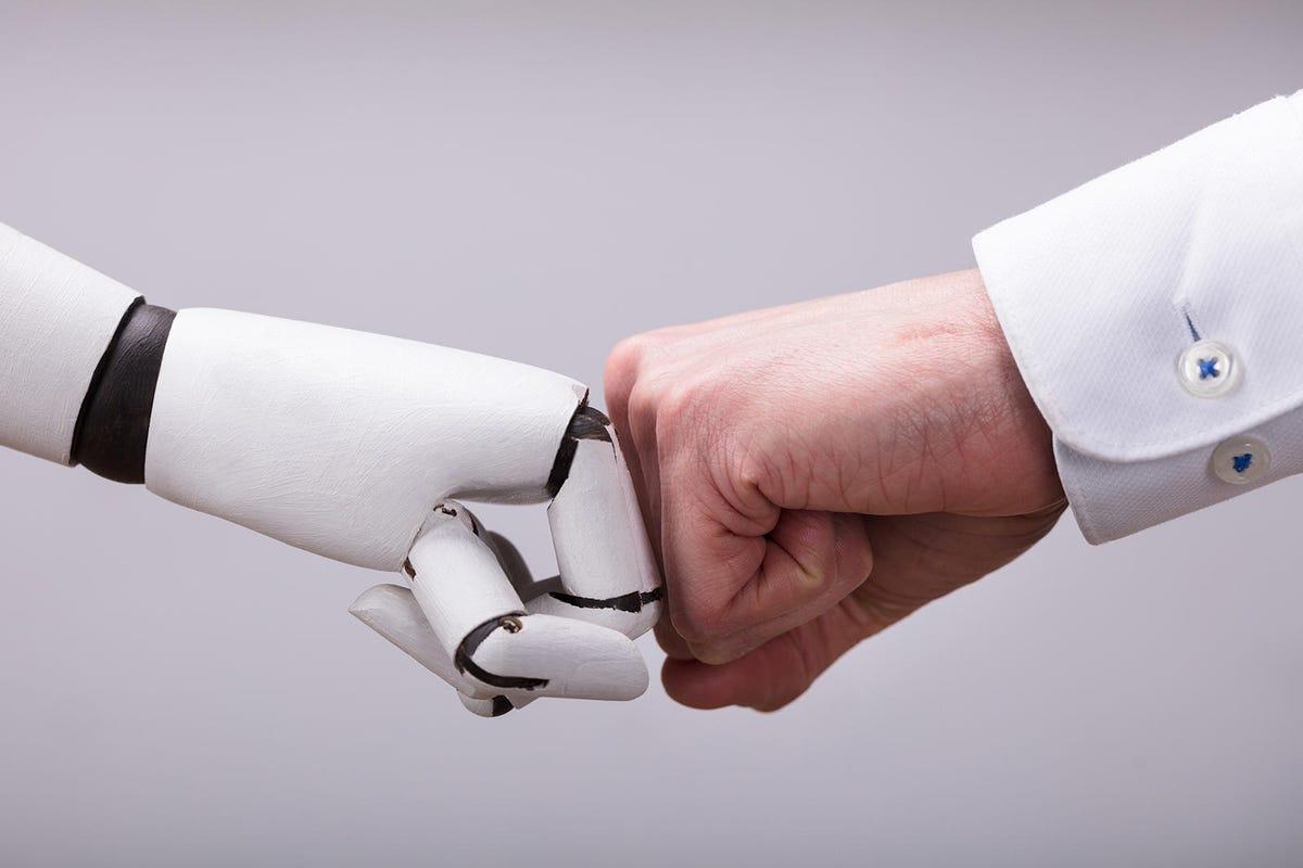 Robot And Human Hand Making Fist Bump