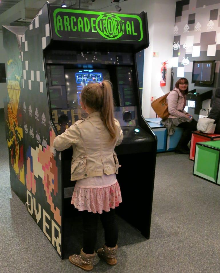 Small girl versus large arcade machine