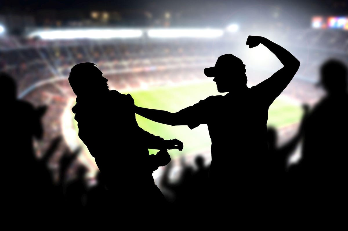 Fight in a football game crowd. Angry man hitting another spectator in soccer match audience. Violent argument between two fans of different teams and clubs.