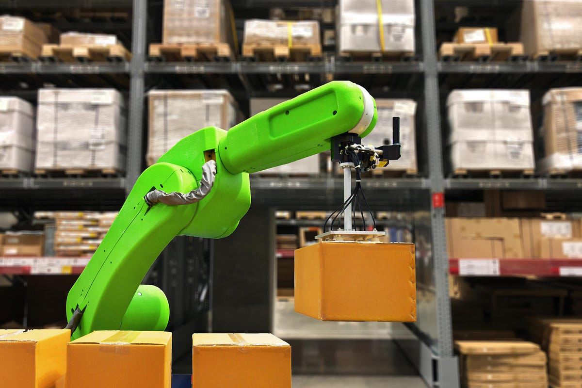 Industrial robot holding a box operating a robot machine