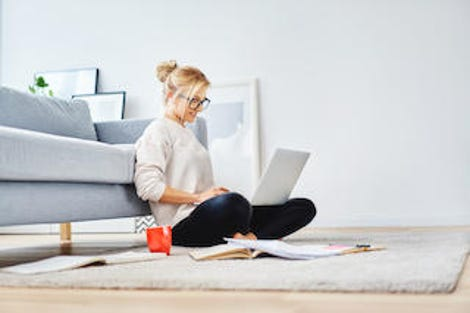 Female student sitting on floor of her apartment with laptop and notes studying