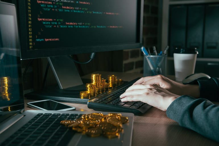 istock-hacker-at-a-desk-with-bitcoin.jpg