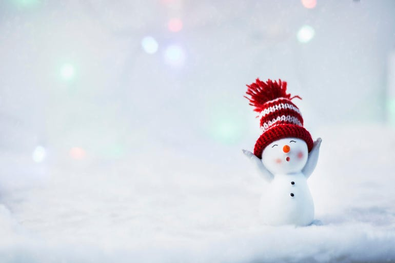 Happy snowman standing in winter christmas landscape. Merry christmas and happy new year greeting card. Funny snowman in hat on snowy background. Copy