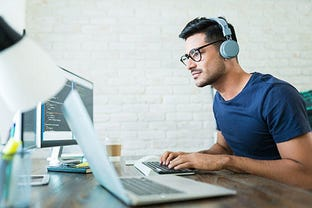 Latin Freelance Coding Expert Using Computer At Desk