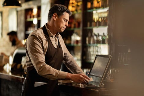 Male waiter going through orders while working at cash register in a bar.
