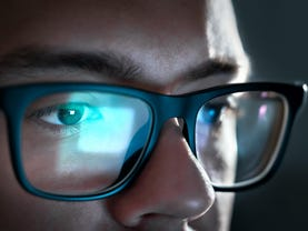 Light from the computer screen reflects off the glasses.  Close-up on the eyes.  Businessman, coder or programmer working late at night with laptop.  Concentrated guy thinking in the dark.
