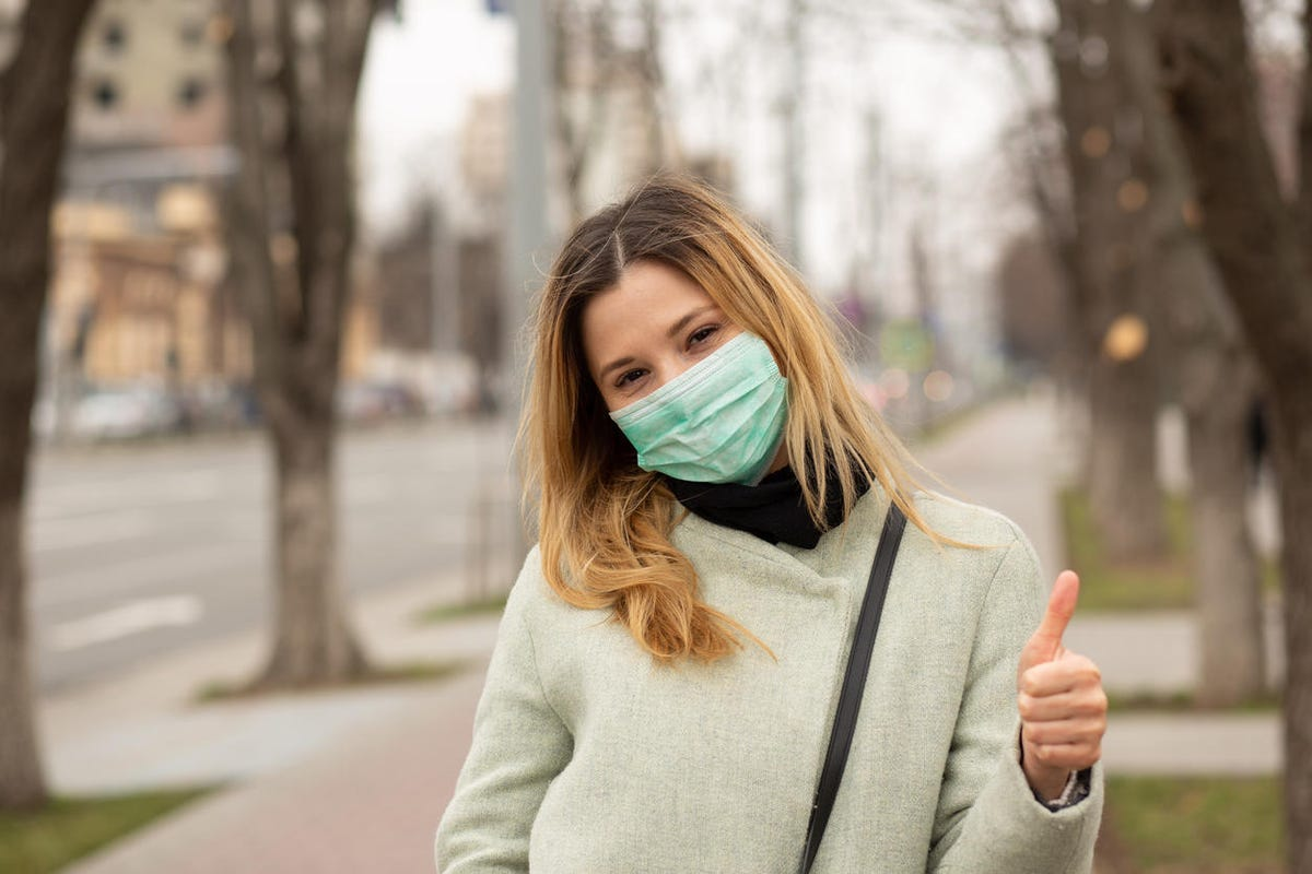 young woman in medical sterile protective mask on her face, walking in a European city, showing thumbs up