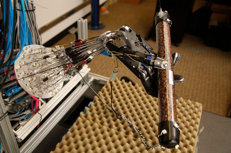 a dexterous robotic hand grasps a cylinder