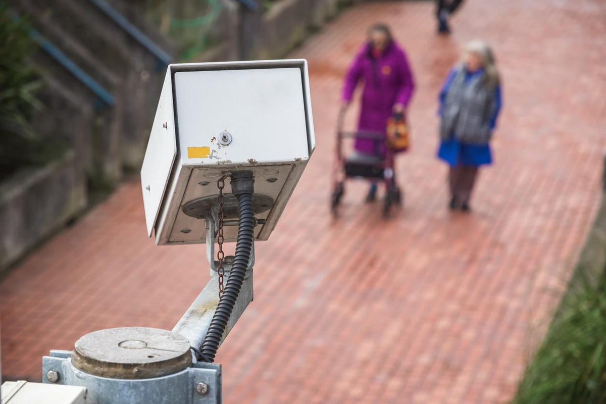 Surveillance camera with unidentified walking elderly people in the background
