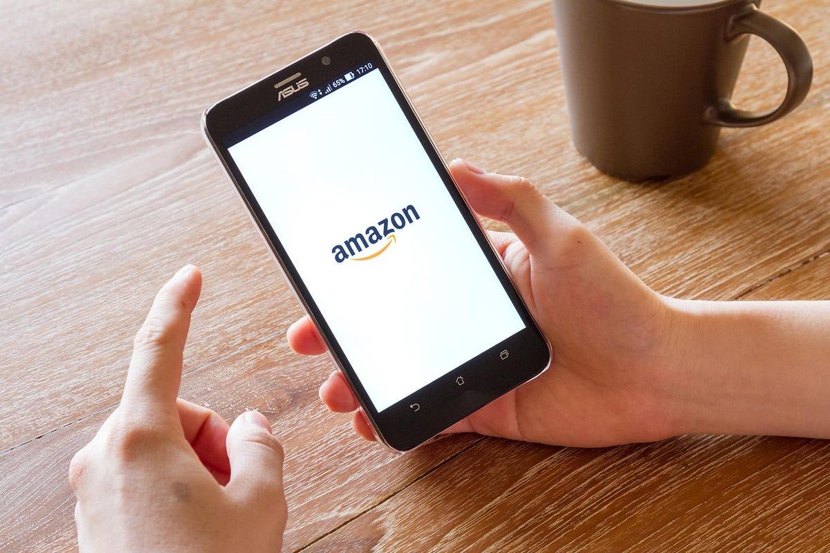 man hand holding screen shot of Amazon application