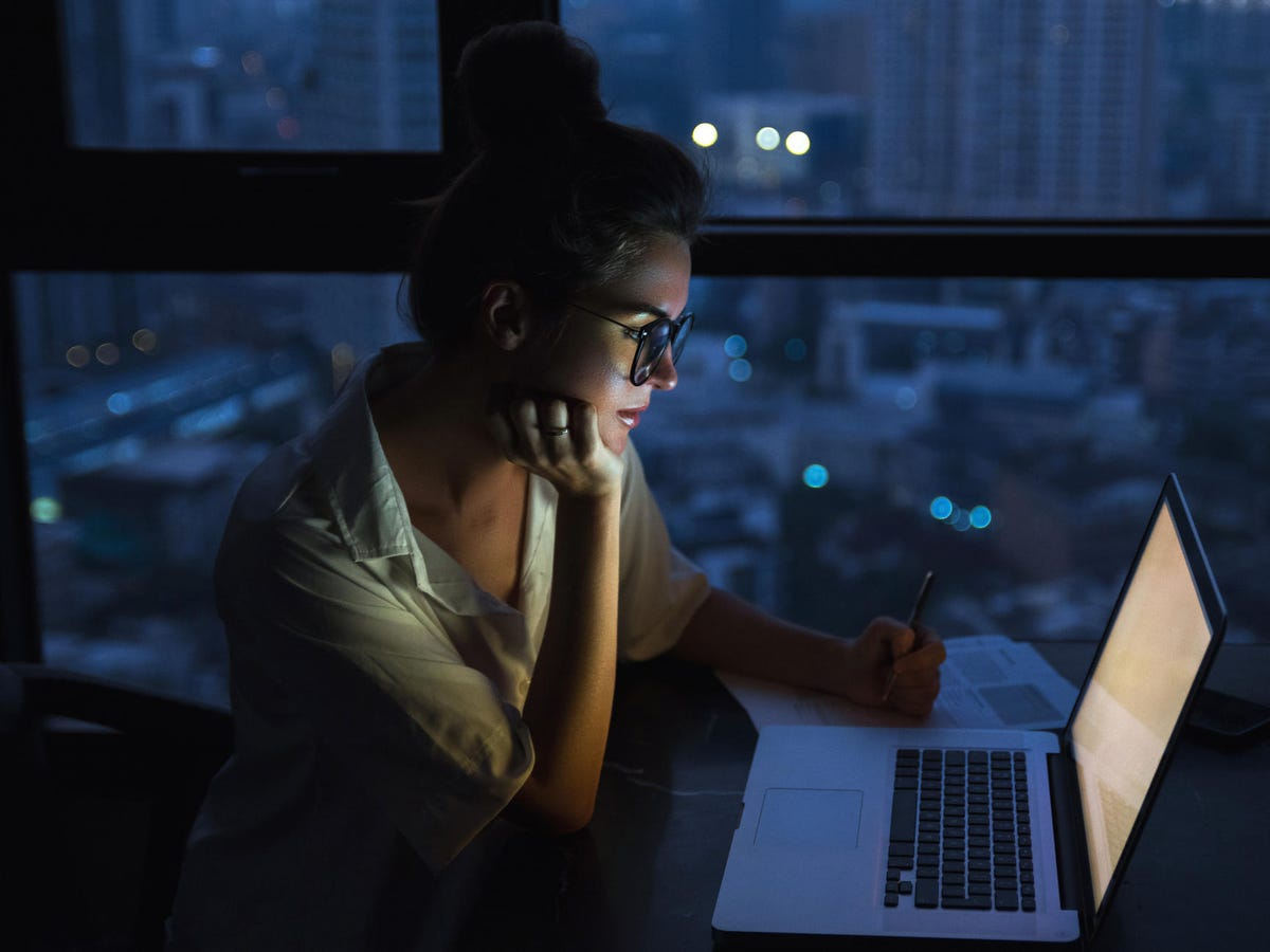 Developer with laptop at night.