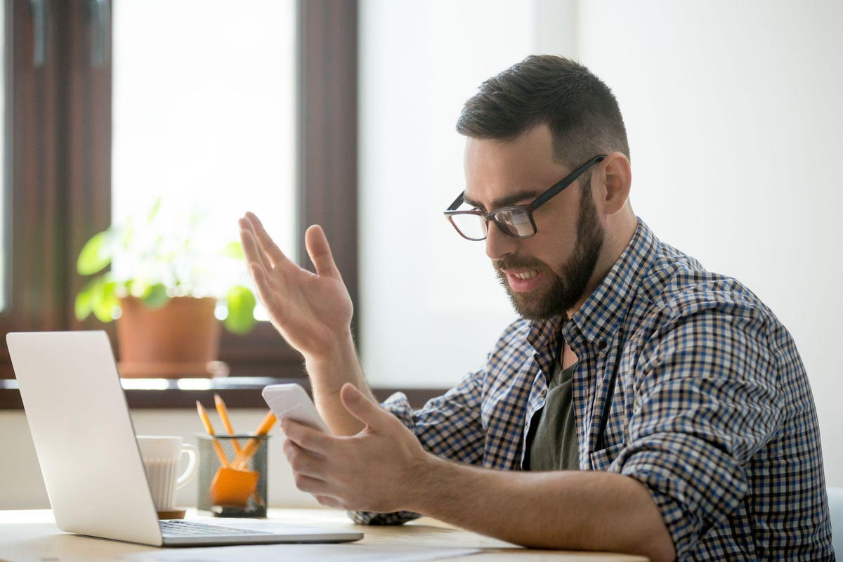 Angry bearded businessman annoyed with phone call in office