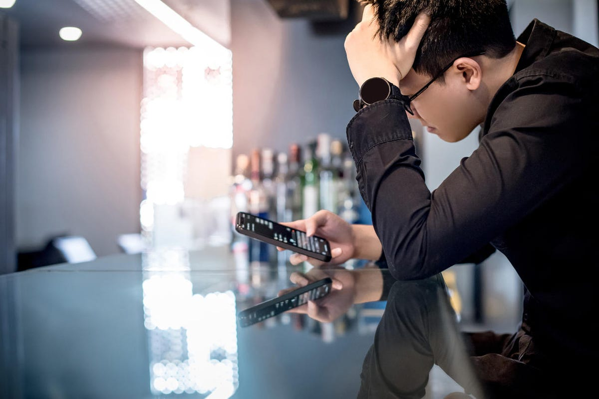 Asian man feeling stress while using smartphone